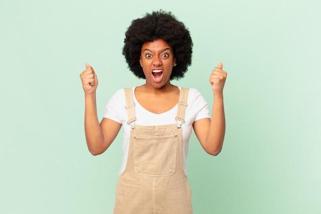 Афро-женщина агрессивно кричит с сердитым выражением лица или со сжатыми кулаками, празднуя успех концепции шеф-повара