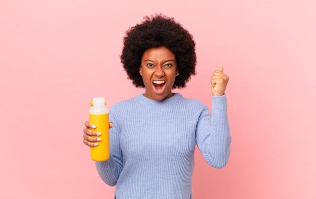 Афро-женщина агрессивно кричит с сердитым выражением лица или со сжатыми кулаками, празднуя успех. концепция смузи