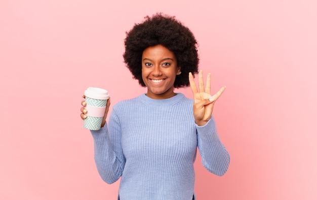 Афро-женщина улыбается и выглядит дружелюбно, показывает номер четыре или четвертый с рукой вперед, отсчитывая. концепция кофе