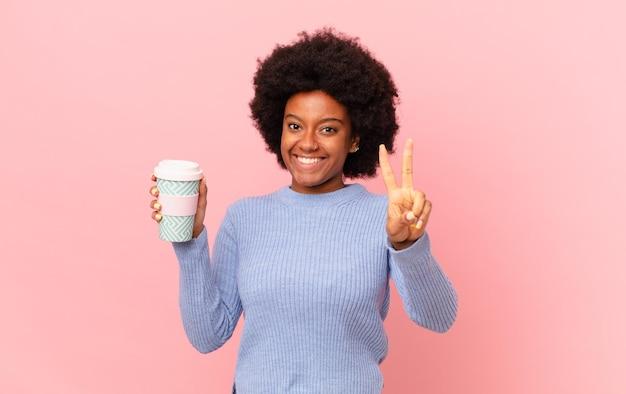 アフロの女性は笑顔で幸せそうに見え、のんきで前向きで、片手で勝利または平和を身振りで示します。コーヒーのコンセプト