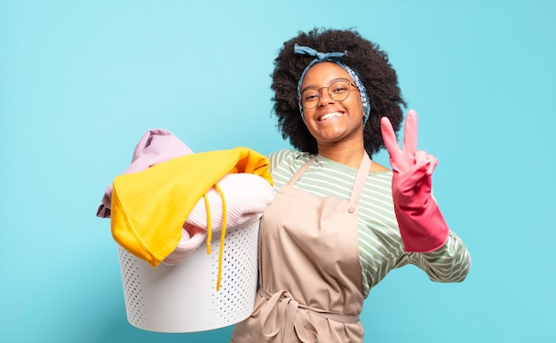 Афро женщина улыбается и выглядит счастливой, беззаботной и позитивной, жестикулируя победу или мир одной рукой. концепция домашнего хозяйства