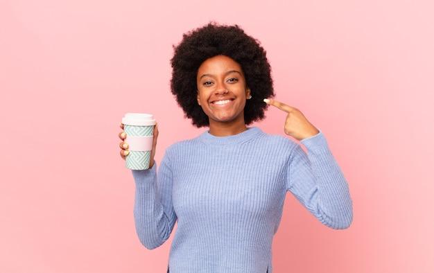 자신의 넓은 미소, 긍정적이고, 편안하고, 만족스러운 태도를 자신있게 가리키며 웃고 있는 아프리카 여성. 커피 컨셉