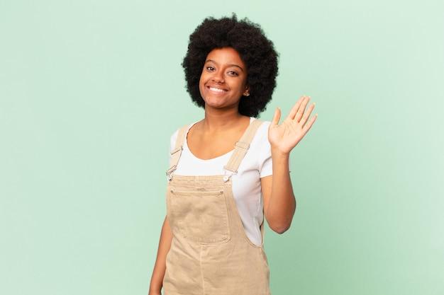 Афро-женщина счастливо и весело улыбается, машет рукой, приветствует и приветствует вас или прощается с концепцией шеф-повара
