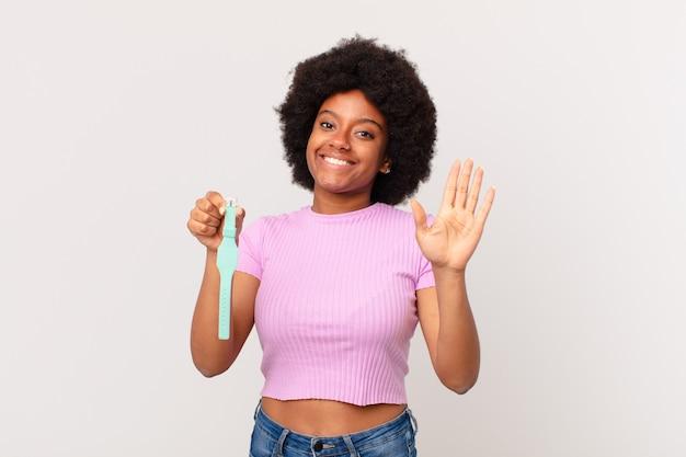 Афро-женщина счастливо и весело улыбается, машет рукой, приветствует и приветствует вас или прощается с концепцией часов