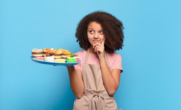 Афро-женщина счастливо улыбается и мечтает или сомневается, глядя в сторону. юмористическая концепция пекаря