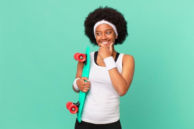 あごに手を当てて幸せで自信に満ちた表情で微笑んでいるアフロの女性は、不思議に思って横を向いています。スケートボードのコンセプト