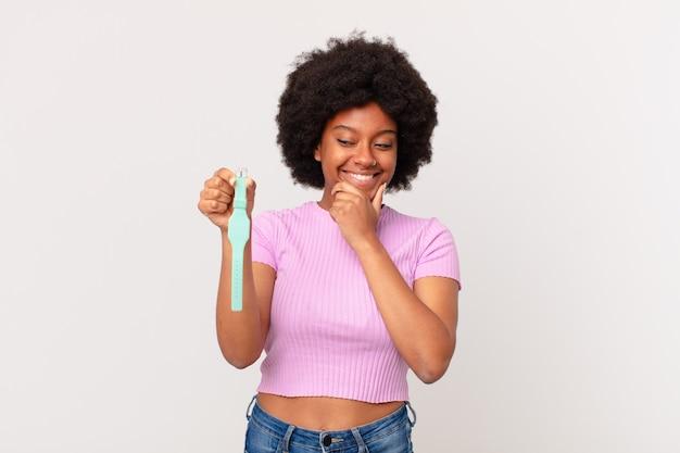 あごに手を当てて幸せで自信に満ちた表情で笑って、不思議に思ってサイドウォッチのコンセプトを見ているアフロの女性
