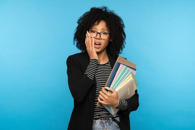Афро-женщина-студентка держит папку и бумажные тетради