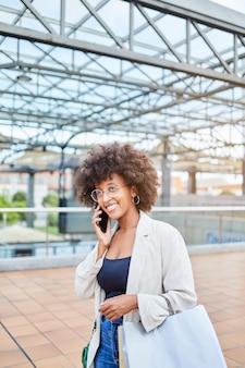 가방을 들고 쇼핑하는 동안 휴대전화로 통화하는 아프리카 여성