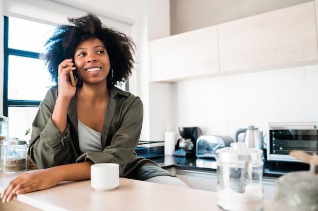 自宅の電話で話しているアフロの女性。