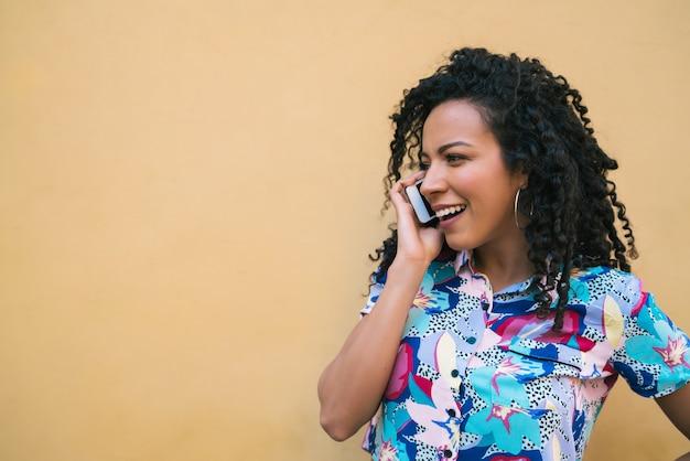 電話で話しているアフロの女性。