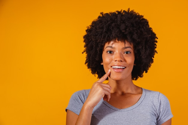 Afro woman thinking on yellow with space for text
