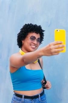 아프리카 여성이 거리를 걷고 휴대전화로 셀카를 찍고 웃고 있습니다.