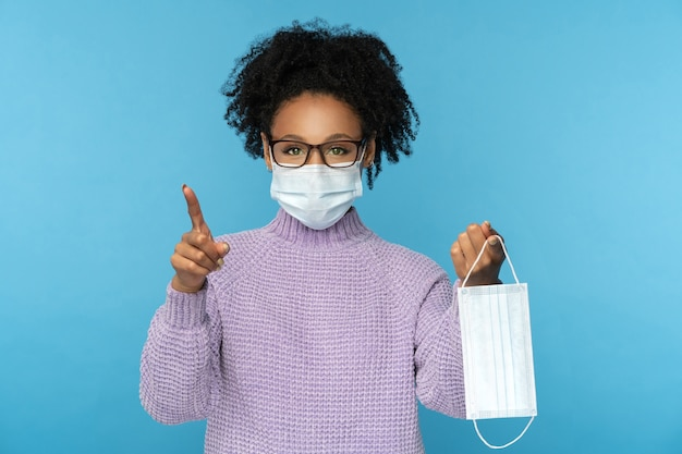 Afro woman wear face mask to prevent from coronavirus isolated on blue