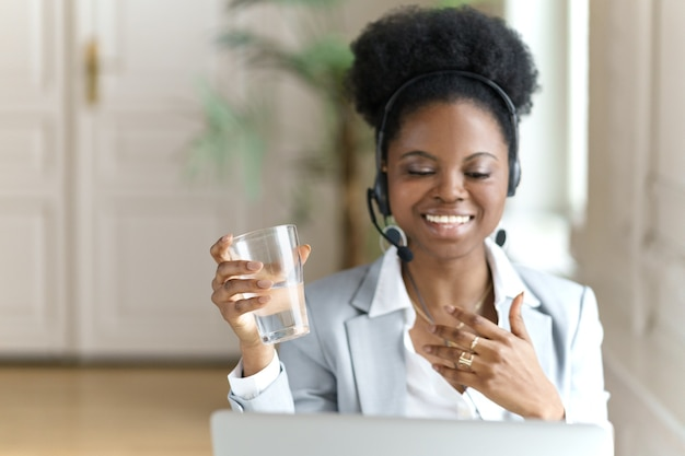 Afro woman wear headphones, work at laptop at office, talking in video chat, holding glass of water