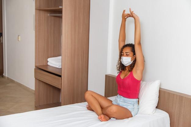 깨어난 후 스트레칭 수술용 마스크를 쓴 아프리카 여성