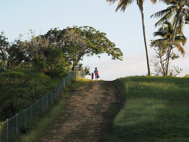 Afro woman with bags and a child walk on a rural road in the morning. tropics environment. back view.