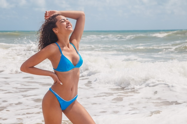 Afro woman with beautiful body on the beach smiling.