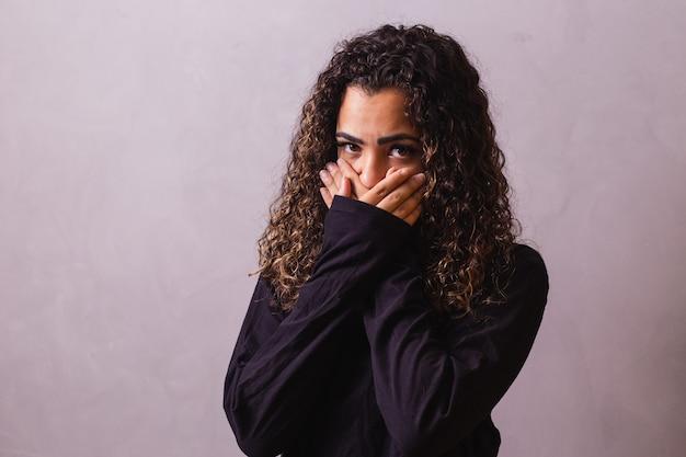 Афро-женщина с рукой во рту, концепция жестокого обращения, феминицид, расизм и предрассудки