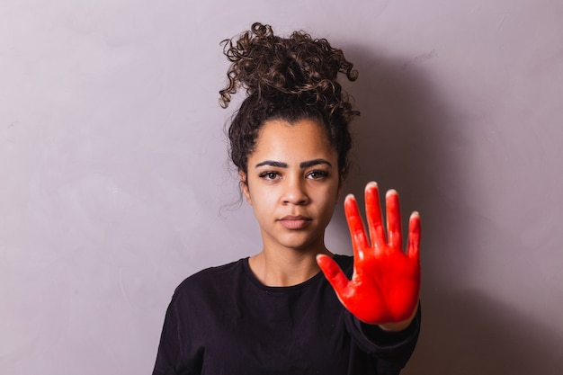 Afro woman with hand painted red with stop concept