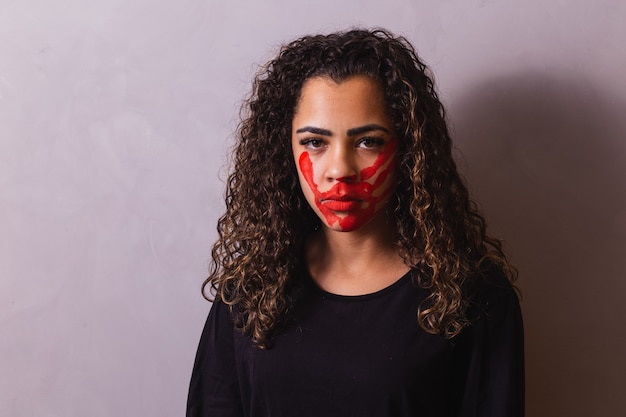 Afro woman with handprint on her mouth in favor of awareness of feminicide. domestic violence