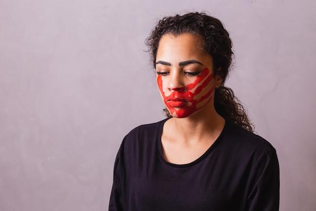 Афро-женщина с отпечатком руки на рту выступает за осведомленность о феминициде. домашнее насилие Premium Фотографии
