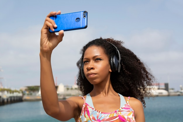 Afro woman with headphones taking a selfie with mobile phone in the background seascape