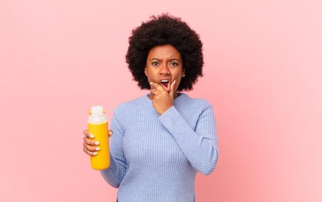 Афро-женщина с широко открытыми глазами и ртом, положив руку на подбородок, чувствуя неприятный шок, говорит что или ничего себе. концепция смузи