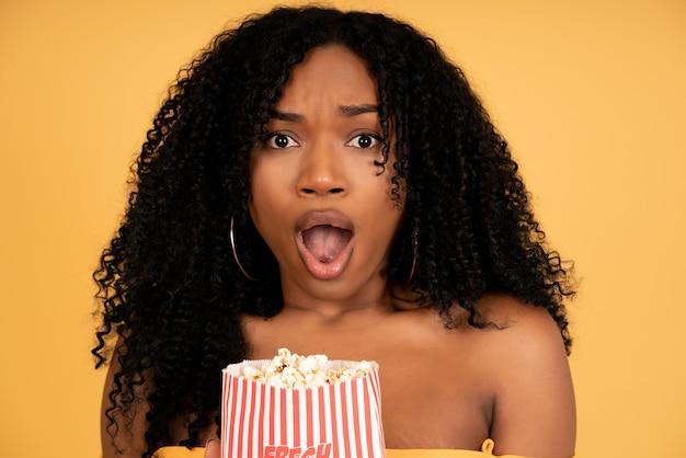 ポップコーンを食べながらショックを受けた表情のアフロ女性。