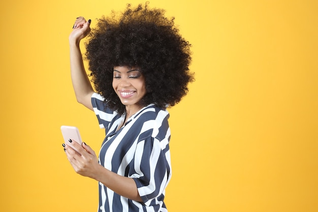 Afro woman, with smartphone dancing on yellow background