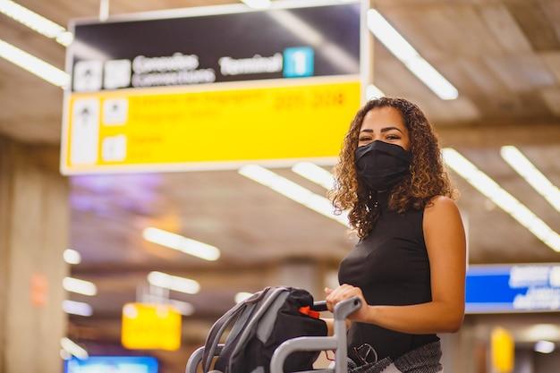 空港でスーツケースを持ったアフロの女性。パンデミックで旅行している空港の女性