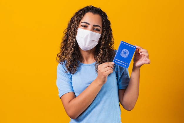 Afro woman with surgical mask holding brazilian work card on yellow background. work, economy and pandemic concept