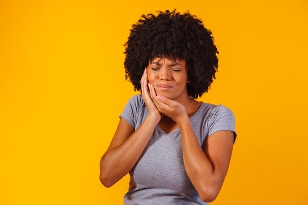 Афро-женщина с зубной болью на желтом