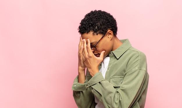 悲しくて欲求不満の絶望、泣き、側面図で目を覆っているアフロの若い黒人女性