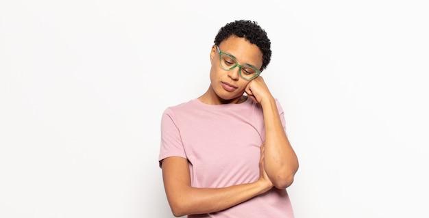 Афро-молодая темнокожая женщина чувствует скуку, разочарование и сонливость после утомительной, скучной и утомительной работы, держа лицо рукой