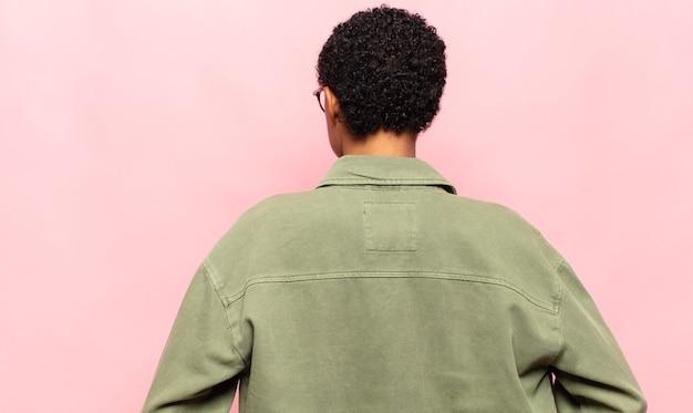 Афро молодая темнокожая женщина, чувствуя себя растерянной или наполненной, или сомнениями и вопросами, недоумевающими, с руками на бедрах, вид сзади