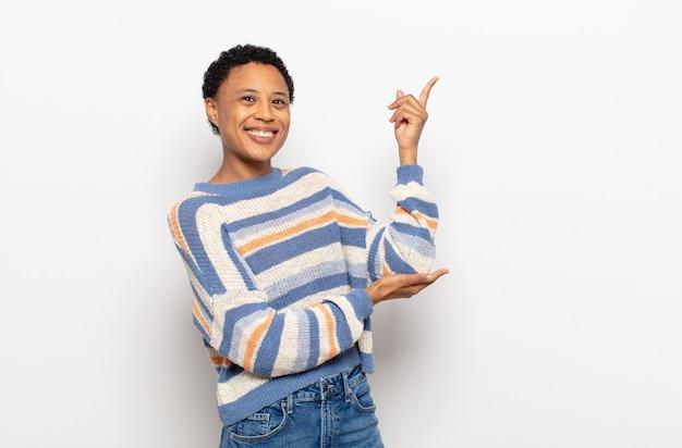 幸せで陽気に感じ、笑顔であなたを歓迎し、フレンドリーなジェスチャーであなたを招待するアフロの若い黒人女性