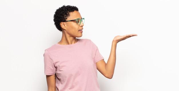 아프리카 젊은 흑인 여성이 행복을 느끼고 자연스럽게 웃고, 물건이나 개념을 찾고 있습니다.