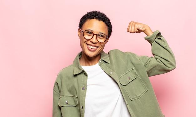 アフロの若い黒人女性は、幸せで、満足していて、力強く、体を曲げて、筋肉質の上腕二頭筋を感じ、ジムの後で強く見えます