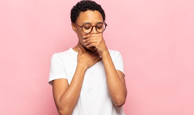 Афро молодая чернокожая женщина чувствует себя больной с симптомами гриппа и болью в горле, кашляет с прикрытым ртом