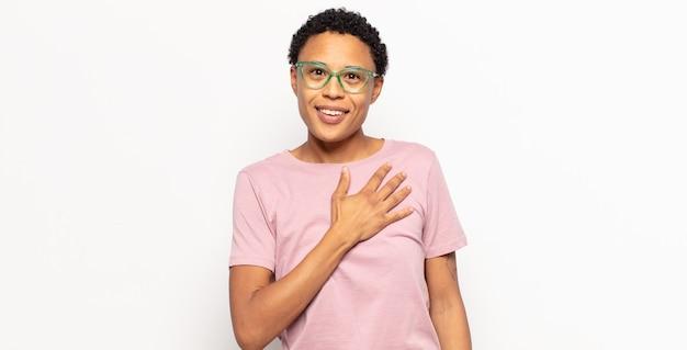 アフロの若い黒人女性は、ショックを受けて驚き、笑顔で、心に手を取り合って、一人になって幸せであるか、感謝の気持ちを示しています