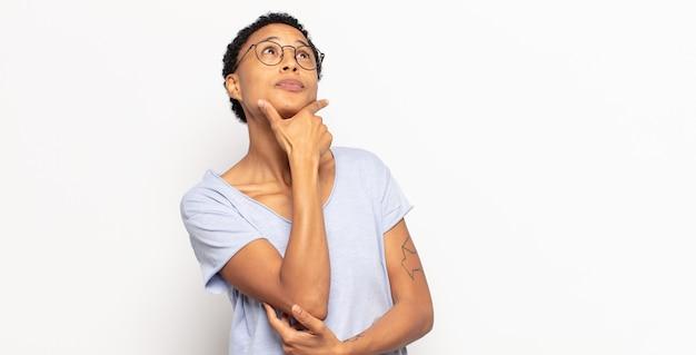 アフロの若い黒人女性は、思慮深く、疑問に思ったり、想像したり、空想にふけったり、コピースペースを見上げたりしています。