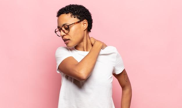 Афро-молодая темнокожая женщина чувствует усталость, стресс, тревогу, разочарование и депрессию, страдает от боли в спине или шее