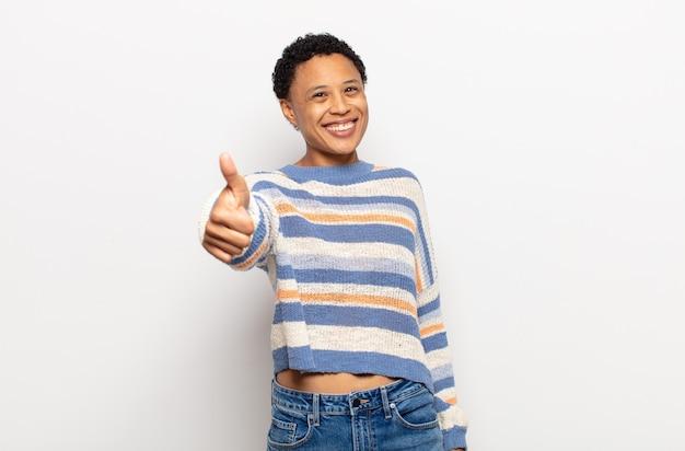 Афро-молодая темнокожая женщина выглядит счастливой, высокомерной, гордой и самодовольной, чувствуя себя номером один