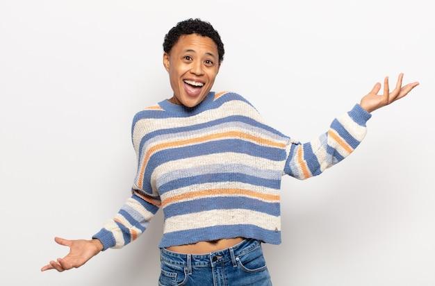 Афро-молодая черная женщина выглядит гордой, высокомерной, счастливой, удивленной и удовлетворенной, указывая на себя, чувствуя себя победителем