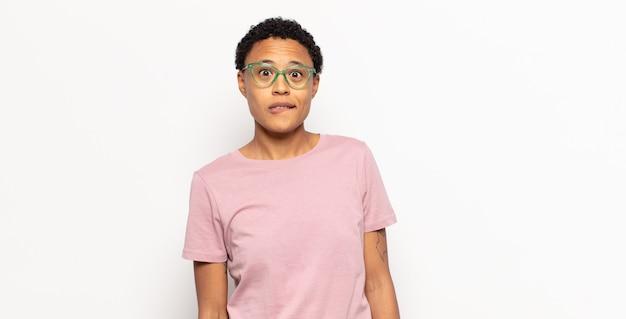 Афро-молодая темнокожая женщина выглядит озадаченной и сбитой с толку, нервно прикусывает губу, не зная ответа на проблему