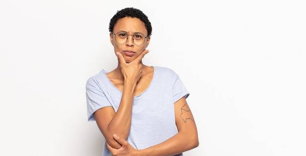 Afro young black woman looking serious, thoughtful and distrustful, with one arm crossed and hand on chin, weighting options