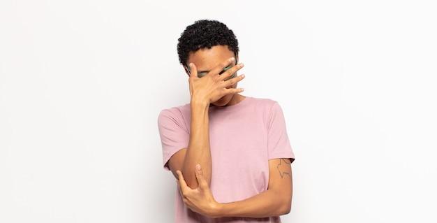 ストレス、恥ずかしがり屋、または動揺して、頭痛で顔を覆っているアフロの若い黒人女性
