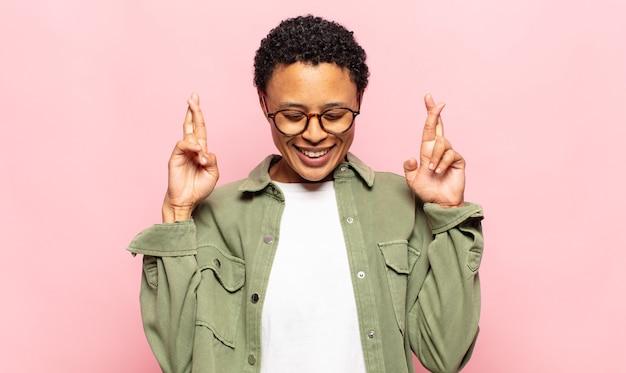 아프리카 젊은 흑인 여성이 웃고 걱정스럽게 두 손가락을 교차하고 걱정하고 소원을 빌거나 행운을 기대합니다.