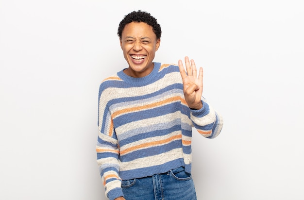 Afro young black woman smiling and looking friendly, showing number four or fourth with hand forward, counting down